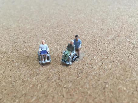 Elderly people in wheelchairs and caregivers