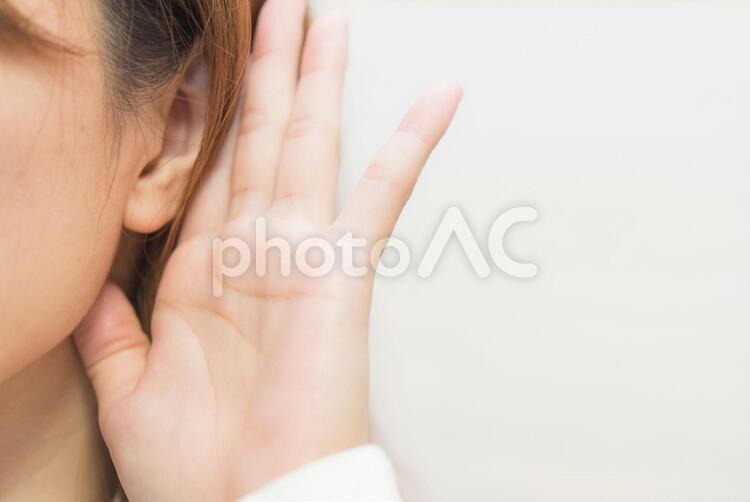 耳に手をあてる女性の写真