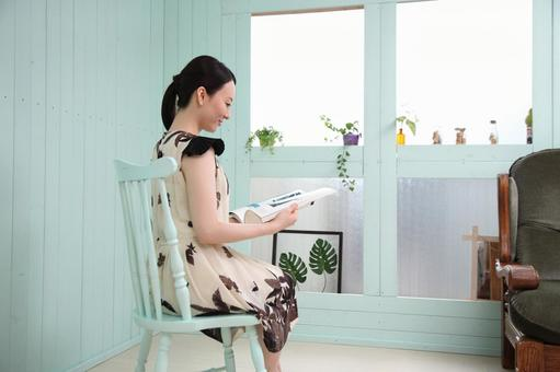 A woman sitting in a chair and reading a book 3