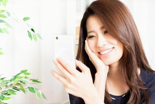 A smiling woman looking at a smartphone