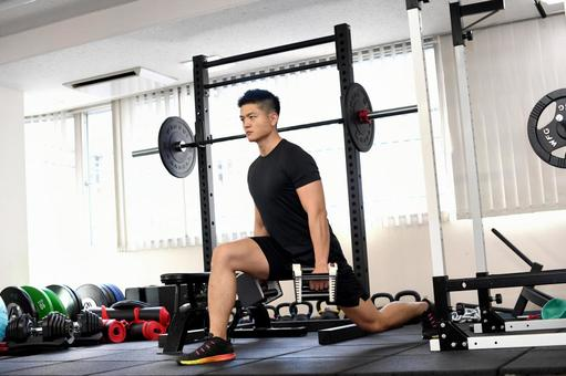 Young man training (lunge) in the gym