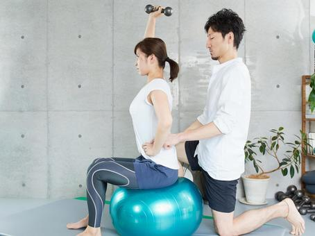 Japanese woman receiving dumbbell training guidance from a personal trainer