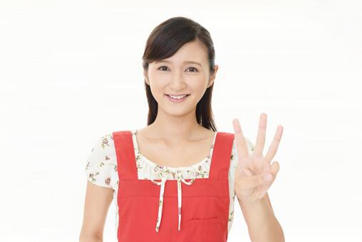 A woman who represents the number three with her fingers