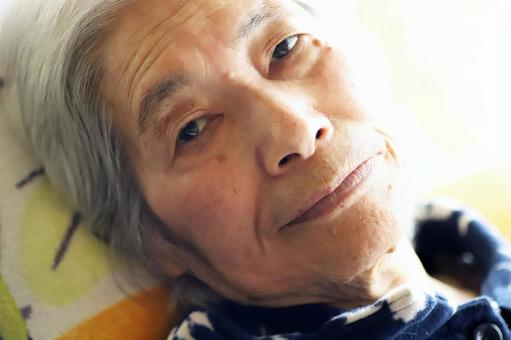 Close-up of a senior woman looking at the camera lying on a nursing bed