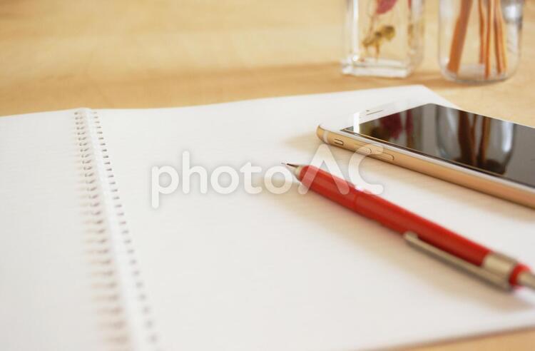 ノートとスマートフォン デスクイメージの写真