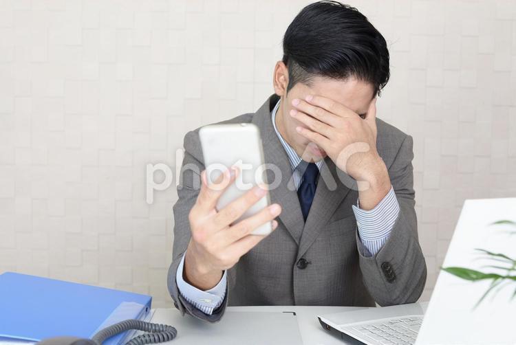 スマートフォンを持つ男性 ストレスの写真