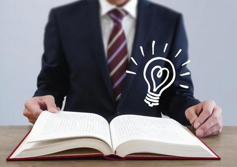 A businessman and a light bulb opening a thick book