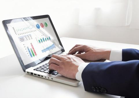 Male businessman working on a graph screen PC