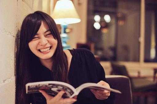 A woman reading a magazine at a cafe and laughing
