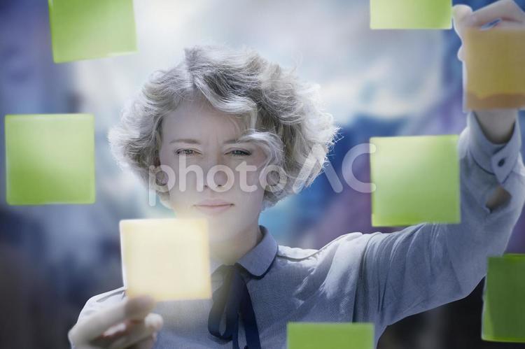 たくさんの付箋を貼る女性の写真