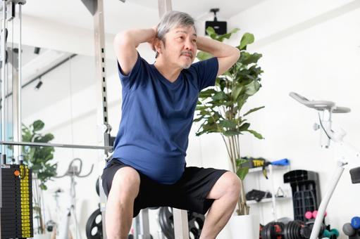 White-haired senior man squatting in the gym