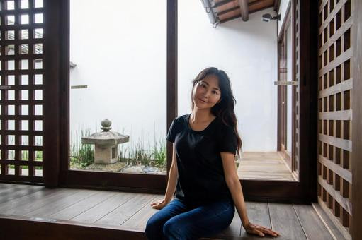 A smiling woman in an old folk house with a garden