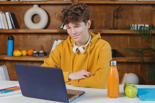 Teenage boy taking online lessons at the table