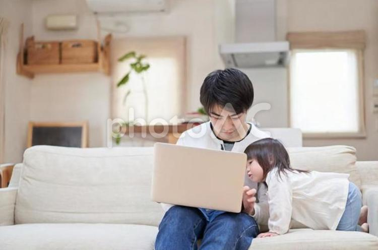 テレワーク中のパパの邪魔をするアジア人の子供の写真