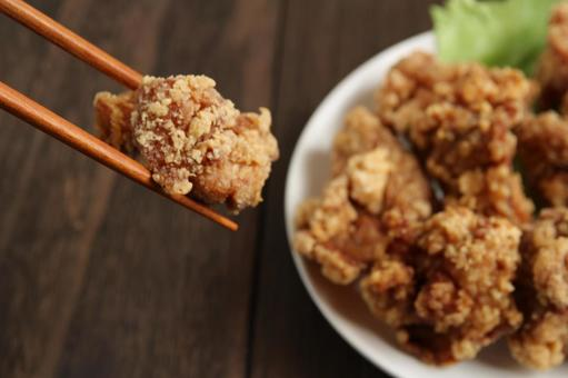 Lift the fried chicken with lettuce on a wooden table with chopsticks