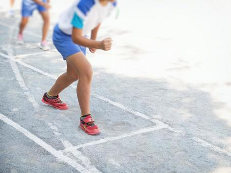Elementary school students preparing for a foot race at an athletic meet