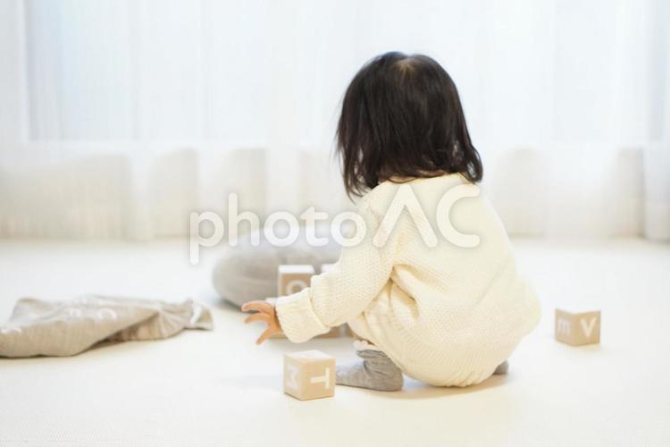 積み木で遊ぶ女の子の後姿の写真