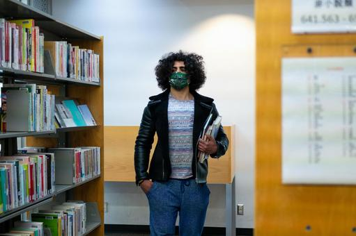 Afro-headed man walking between bookshelves