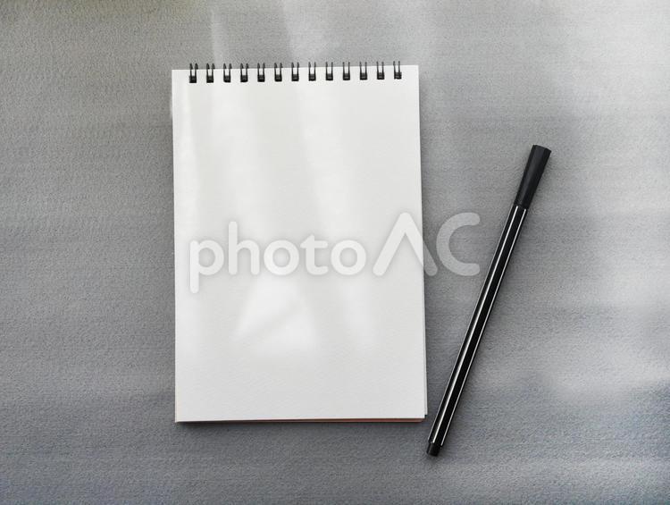 紙とペン おしゃれなグレー背景の写真