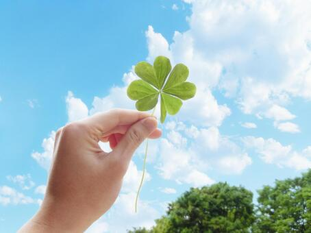 Hand with four-leaf clover and blue sky