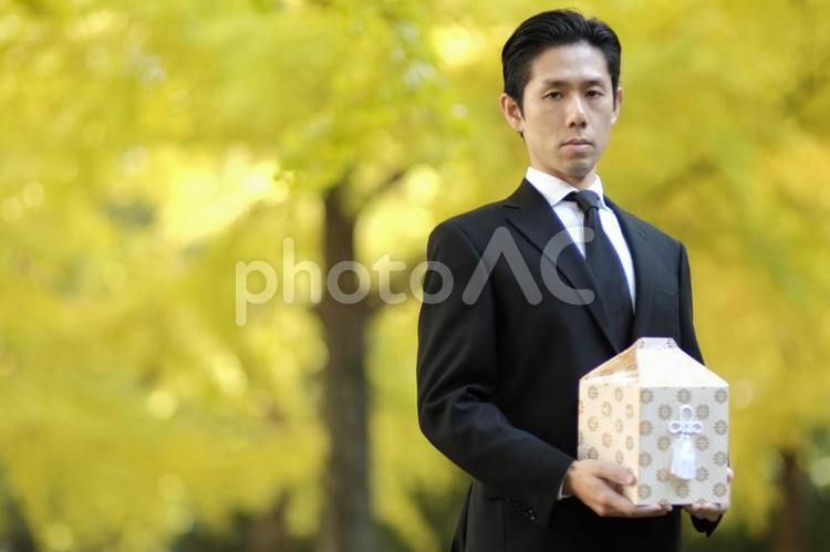 骨壷を持つ男性11の写真