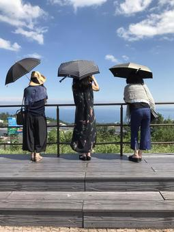 Summer sky, parasol and three women