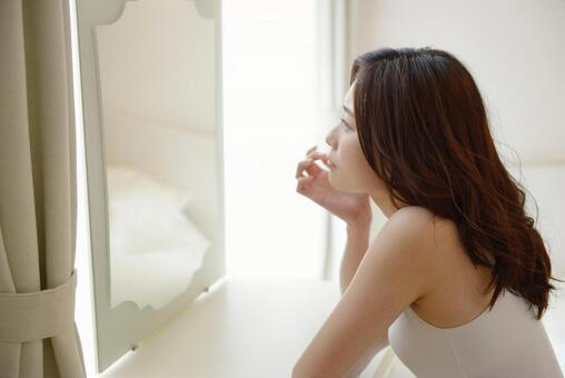 A woman looking at a mirror 1