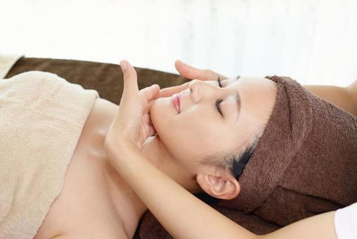 A woman receiving a facial massage at an esthetic salon