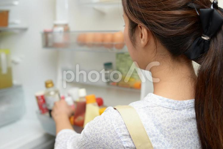 冷蔵庫から調味料を取り出す女性の写真