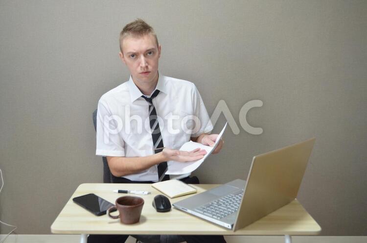 企画書とあきれ顔の会社員の写真