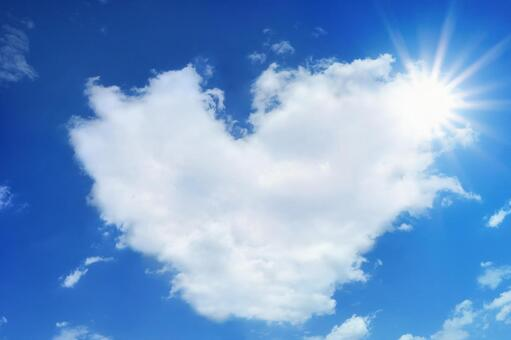Summer sun and heart shaped clouds and blue sky