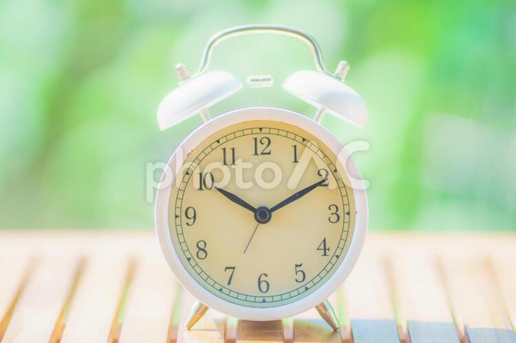 緑ぼかし背景と目覚まし時計の写真
