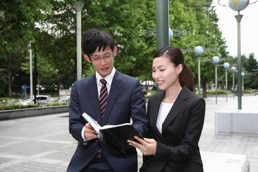 Businessman looking at a notebook, business woman 2