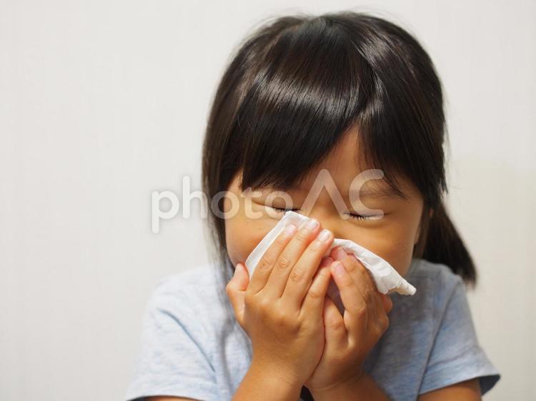 くしゃみをする女の子の写真