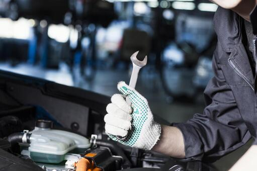 Automobile mechanic who opens the hood and uses the spanner 3