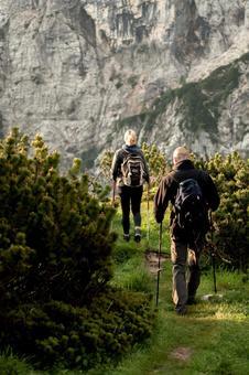 Trekkers of men and women walking toward the rock wall 2
