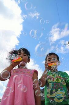 Girls and boys playing with soap bubbles