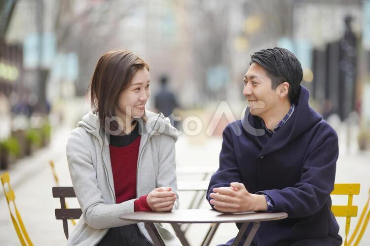 座って談笑するカップルの写真