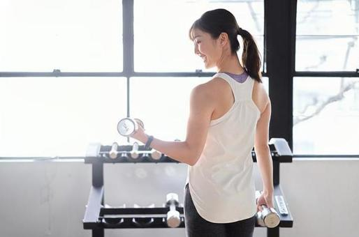 Asian woman with dumbbells in a training gym