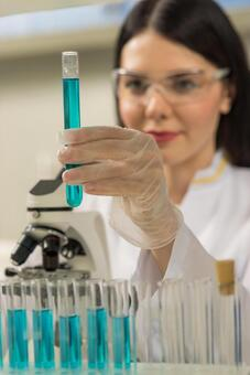 Female researcher looking at a test tube 30