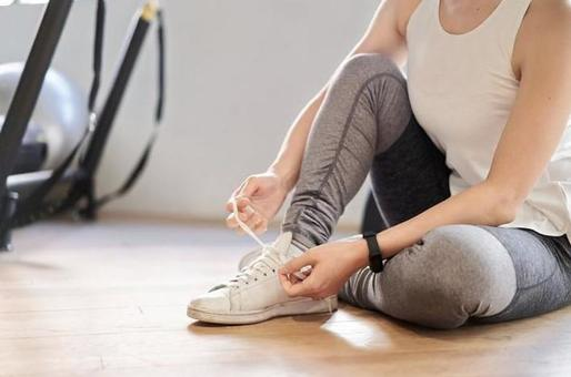Asian woman tying shoelaces in a training gym