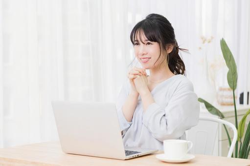 방에서 노트북을 사용하면서 부탁 제스처를하는 젊은 여성