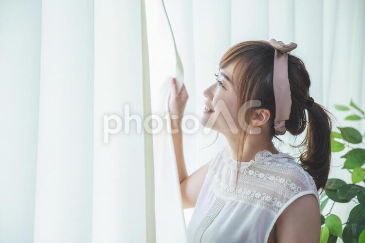 白いカーテンから差し込む朝日を浴びる若い女性の写真
