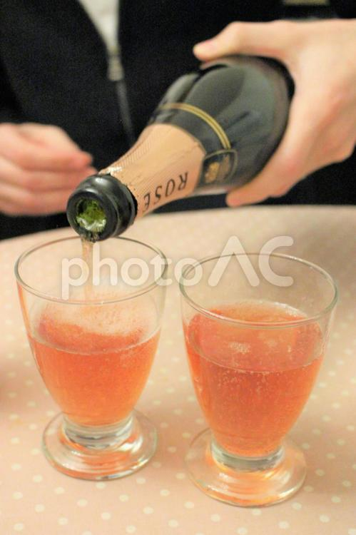 ロゼシャンパンを注ぐ外国人男性の写真