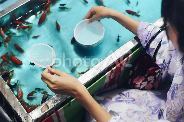 A Japanese girl holds a scooper with a left hand and hold a ball  with a right hand, doing Kingyo sukui (goldfish scooping)