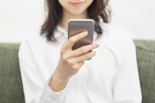 一個女人坐在沙發上,操作智能手機