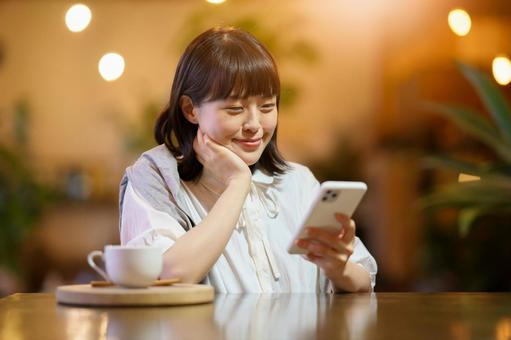 A young woman looking at a smartphone screen in a warm atmosphere