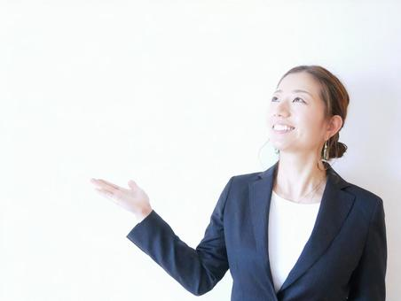 A smiling woman wearing a suit and raising her hands