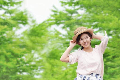 A woman with a smile wearing a forest and a hat