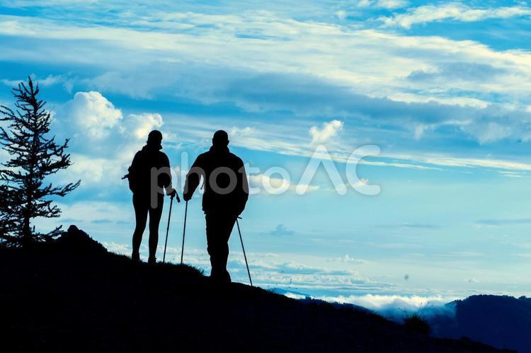 雲の多い空と男女のトレッカーのシルエット2の写真